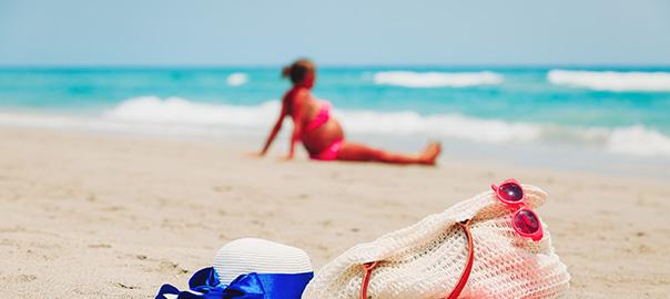 Zwangere vrouw in bikini op het strand